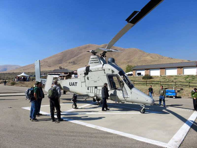 "Federal firefighting managers peruse the ''optionally-piloted'' K-MAX helicopter at the Lucky Peak Helibase in Idaho. ""UAT"" on the fuselage stands for Unmanned Aerial Truck."