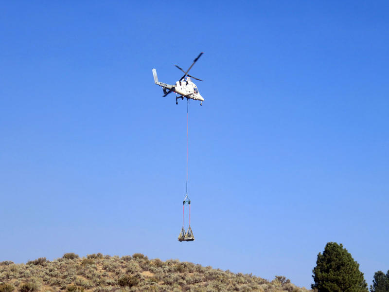 The remotely-piloted K-MAX demonstrates a precision cargo drop on a ridge near Lucky Peak Reservoir Wednesday.