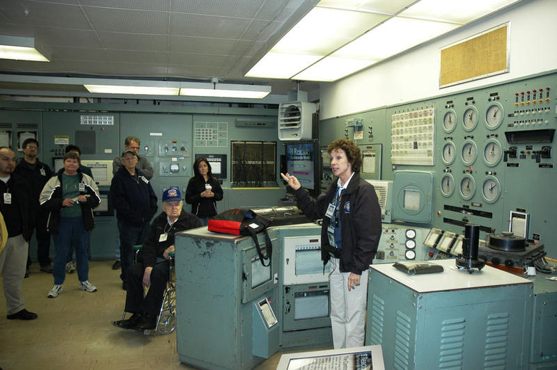 Michele Gerber presents historical information to a tour group inside the Control Room of B Reactor in 2007.