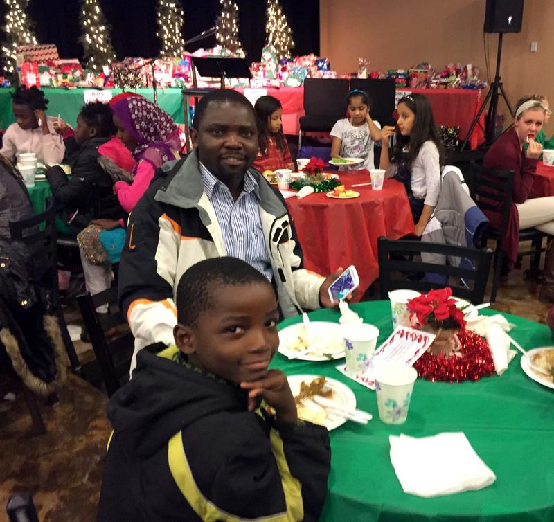 Akembe Bilombele, center, fled war-torn Congo with his family and was resettled in Twin Falls four months ago. ''People in Idaho are very kind,'' he said at a church Christmas party. ''I am very happy here.''
