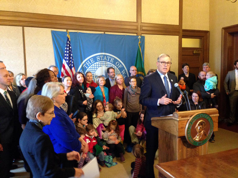 With families and child advocates in the background, Governor Jay Inslee addressed reporters at a Capitol news conference. He applauded the legislature's passage of a pledge to end reliance on local school levies to fund basic education.