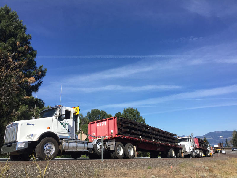 Trucks loaded with replacement railroad tracks were parked outside Mosier, Oregon, over the weekend. Tracks meant to replace those damaged in Friday's train derailment were also brought in by rail.