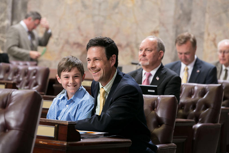 The late Sen. Andy Hill on the floor of the Washington state Senate in 2013 with his son Charlie.