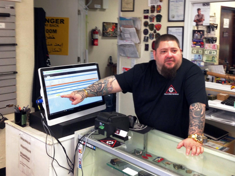 Don Teague of Private Sector Defense, a gun store in Olympia, shows how the FBI's instant background check system works.