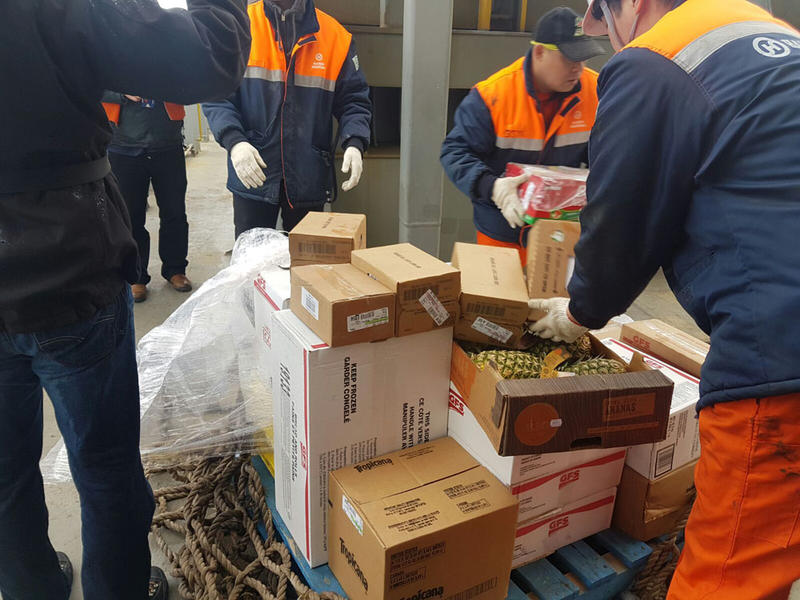 Hanjin Scarlet crew members unpack the pallets of donated provisions that were hoisted aboard in cargo nets.