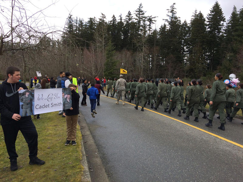 As cadets march towards the park where their families wait to take them home for the weekend, loved ones cheer and hold signs showing their support.