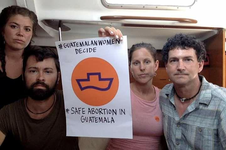 From right, Dan and Merilee Evans of Port Townsend, Washington, hold a poster while detained in a Guatemalan port last week. At left are fellow Women on Waves crew members Alecia Ott and Seth Bearden.