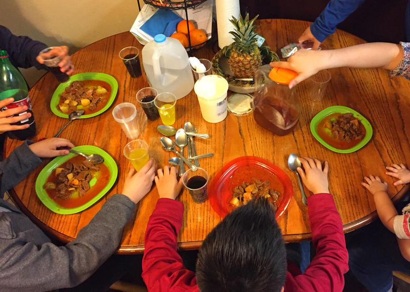 A family of U.S. citizen children sit down to a dinner of carne asada and tortillas with their undocumented mother. Some of the children worry that they'll come home from school and their mother won't be there.