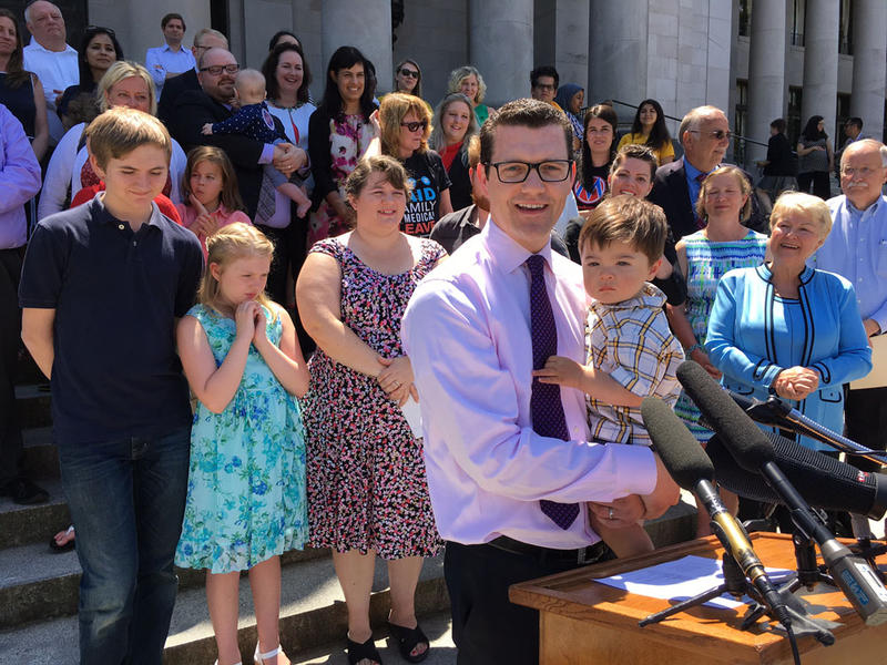 Republican state Senator Joe Fain holds his son as he speaks at a rally celebrating passage of a bipartisan paid family leave bill that was signed into law on Wednesday.