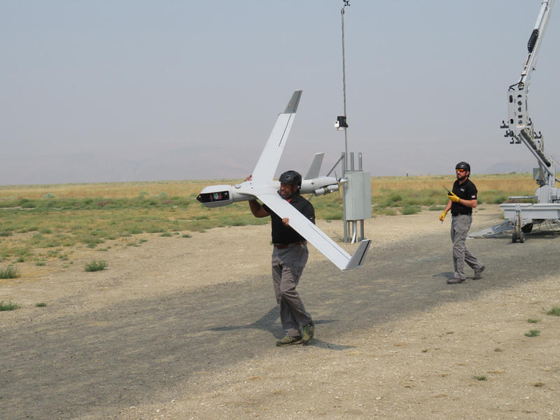 Insitu Flight Demonstration Team member Jeff Kelly carries a ScanEagle drone at the company's flight testing facility in Arlington, Oregon.
