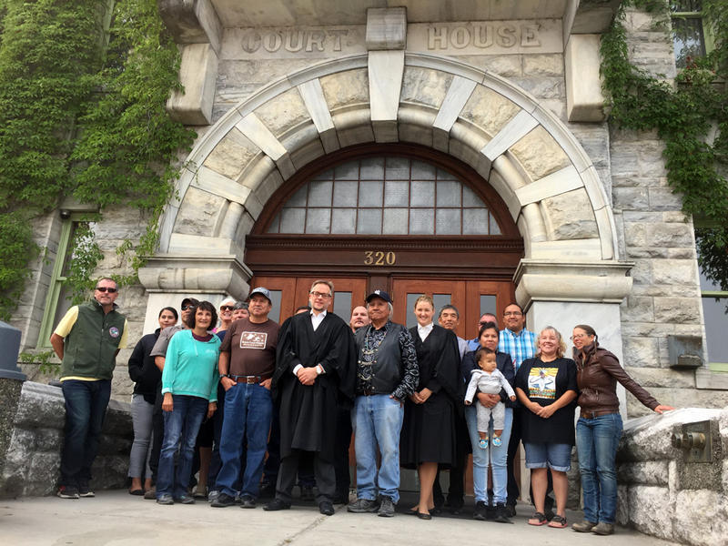 Members of the Sinixt tribe from Washington and Canada, gather outside the courthouse in Nelson, British Columbia with Attorney Mark Underhill, center, in black robes, after three days of arguments in an appeal of a tribal sovereignty case.