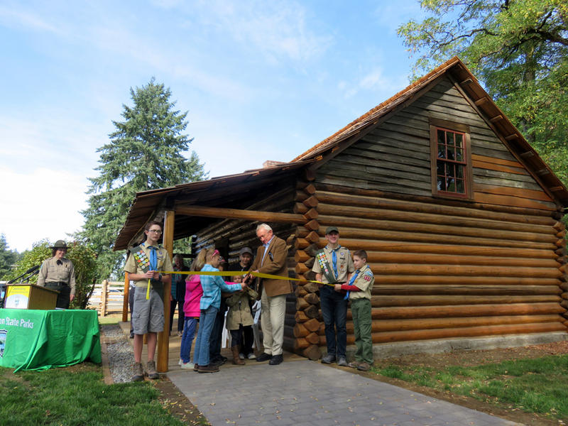 Former Secretary of State Ralph Munro helps to cut a ceremonial ribbon at the rededication of Jackson House State Park on Friday.