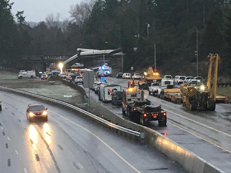 An Amtrak Cascades passenger car dangles from an overpass over Interstate 5 in Pierce County, Washington, after a derailment on Monday morning.