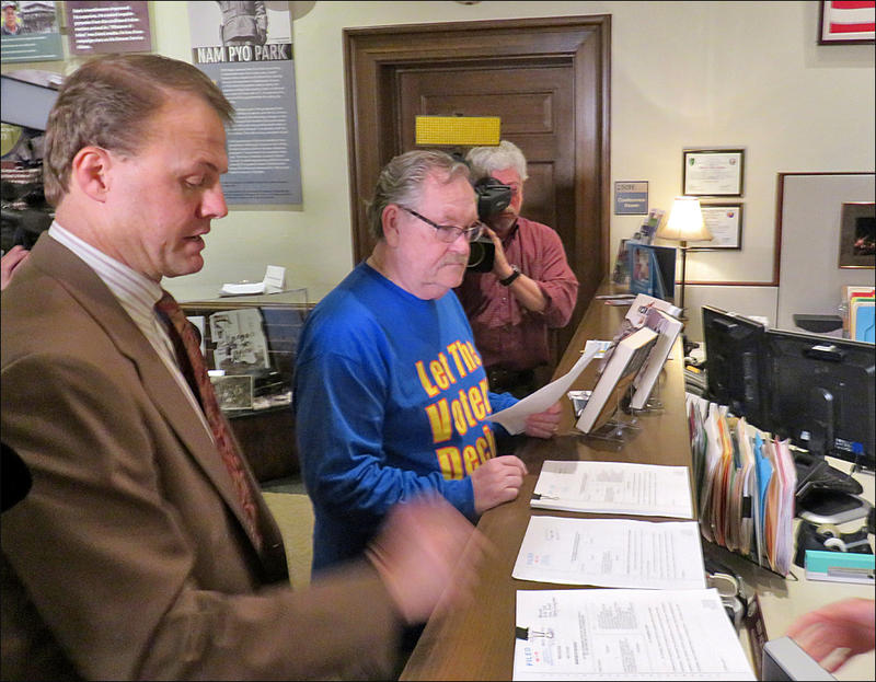 Initiative activist Tim Eyman, left, delivered a copy of his lawsuit to the Secretary of State's office in Olympia Monday.