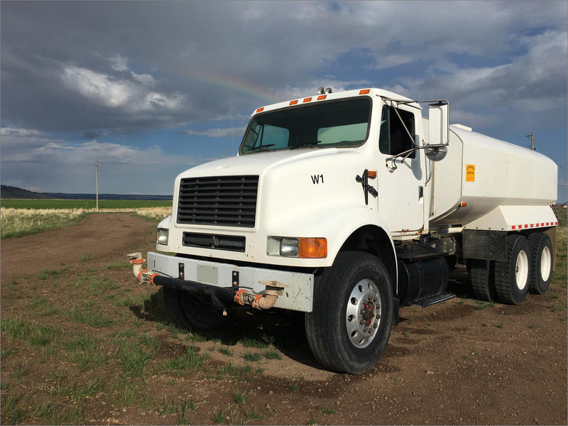 A rainbow brightens the sky above Wayne Evans' water truck near Riley, Oregon. The vehicle can hold a 4,000 gallon load. It will be running every day now through September to bring water to thirsty cattle.