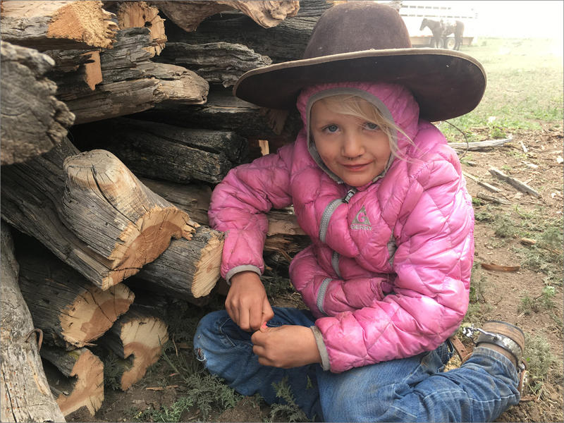 Hayden Miller, 5, seeks shelter behind the branding fire's wood pile. She was looking for a bit of respite from the dust and horse hooves at a community branding.