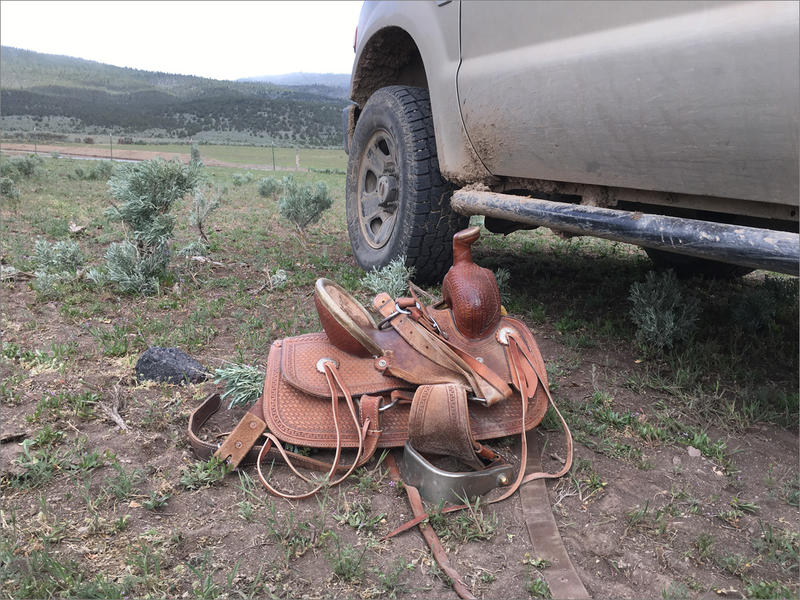 A saddle rests where it was slung in a hurry at a ranch outside of Riley, Oregon. In the distance, Dry Mountain rises up. Soon, cattle will be moved into those mountain meadows, where there's less grass this year because of drought.