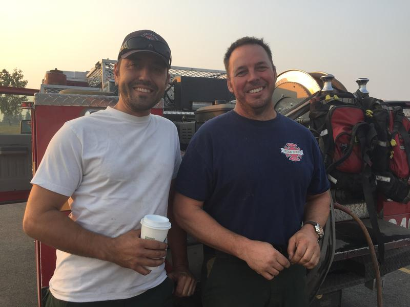 Eric Sadlon (left) and Jonas Smith (right) are firefighters from Seattle. They're helping fight the Silver Lake fire in Cheney outside Spokane, where temperatures have soared past 100 degrees.