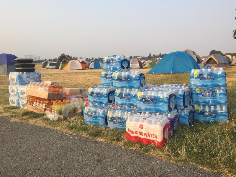 Fire managers are ordering 30 cases of bottled water and 15 cases of Gatorade daily for crews on the Silver Lake fire near Spokane. The tall stacks of beverages dwindle by early morning, as firefighters head out.