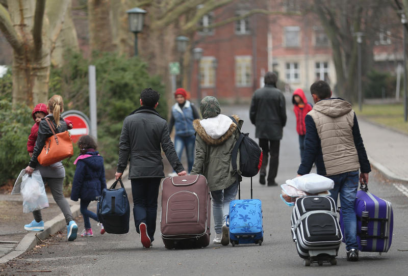 People pulling suitcases arrive at the Central Registration Office for Asylum Seekers in Berli, Germany
