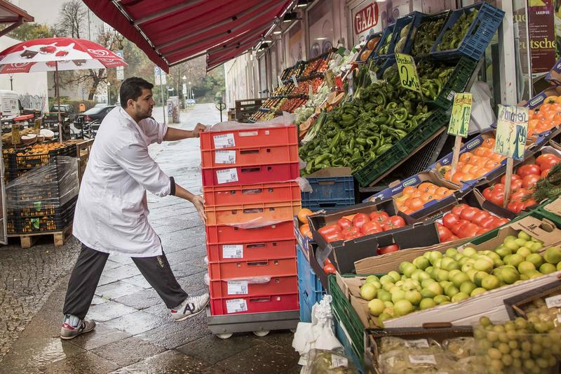 A man carries goods into the Turkish supermarket Marketler at Karl-Marx-Strasse in Neukölln district in this photo dated November 2, 2013.