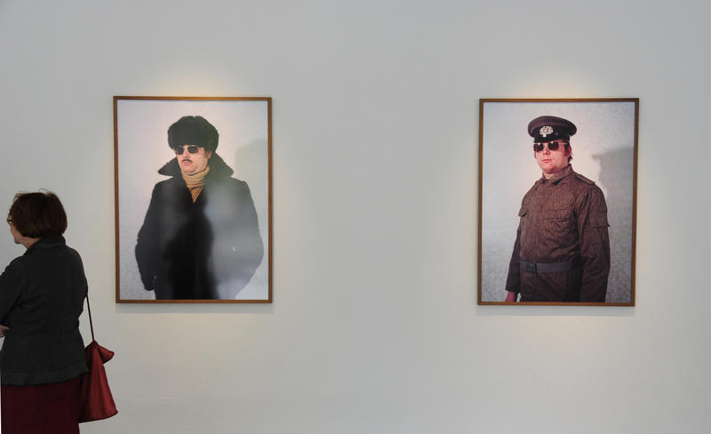 A woman walks past photographs of disguises used by members of the former East German secret police at a Berlin gallery opening in 2011. Simon Menner, the curator, recently gave a talk on his work at the Goethe Institut in Washington, DC.