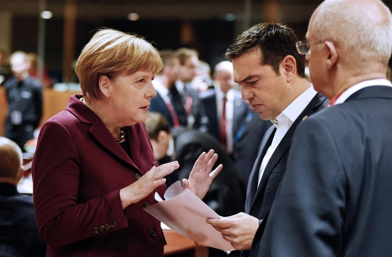 German Chancellor Angela Merkel (L) speaks with Greek Prime Minister Alexis Tsipras before a round table, during a European Union (EU) summit dominated by the migration crisis at the European Council in Brussels, on October 15, 2015.