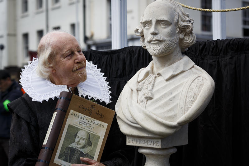 A man dressed as William Shakespeare stares at the famous playwright's statue while holding a book containing completed works by him.