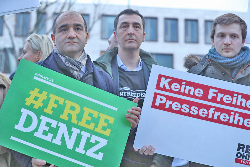 Protesters, including German Greens Party parliamentarians Ozcan Mutlu (L) and Cem Ozdemir (C), gather outside the Turkish Embassy to demand the release of German journalist Deniz Yucel on February 28, 2017 in Berlin, Germany.