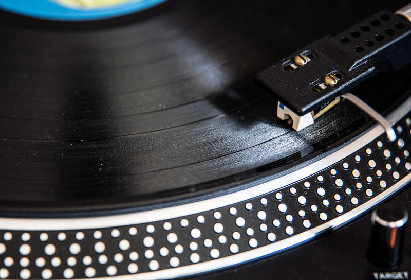 A record dealer in Wanted Records, UK puts on a vinyl record on the shop's turntable. Although sales of vinyl records declined dramatically with the introduction of digital formats such as CDs and downloads, it is now seen as a premium product and sales.