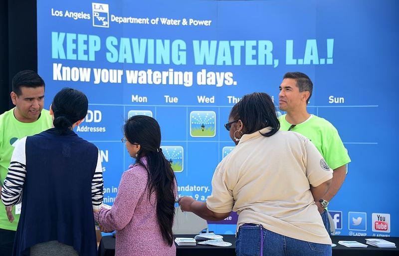 An employee from the Department of Water and Power answers questions about water saving issues at the Grand Park Earth Day celebration in Los Angeles, California on April 22, 2016.