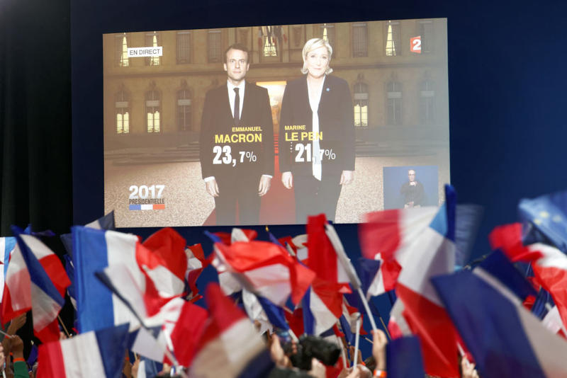 A screen announces the results of the first round of the French Presidential Elections naming Emmanuel Macron with 23.7% and Marine Le Pen with 21.7% of the vote on April 23rd, 2017 in Paris, France.