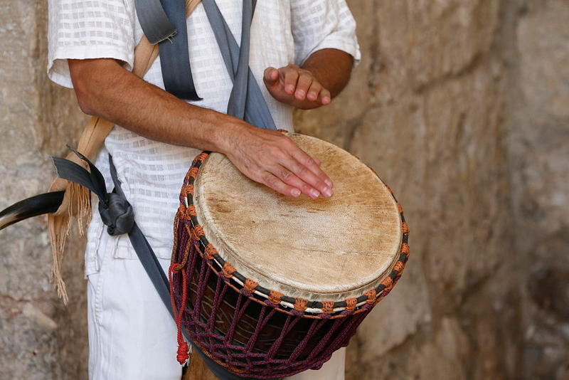 A drummer plays the Djembe, a traditional West African drum.