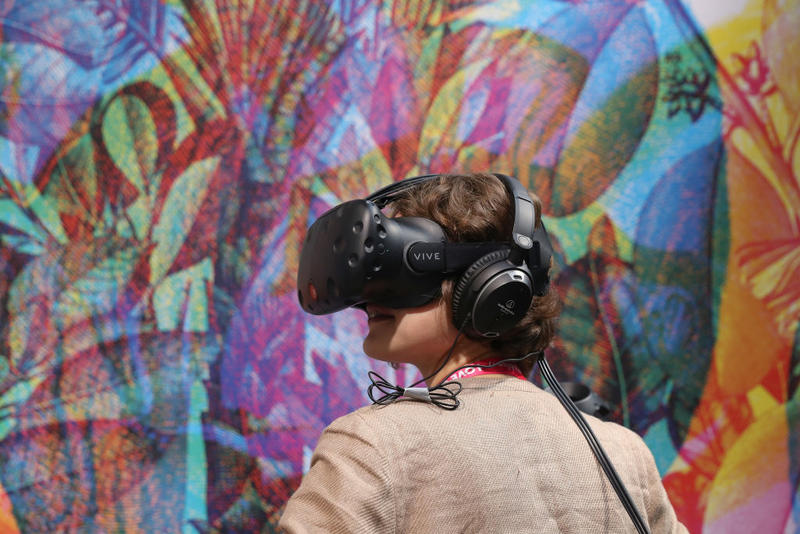 A young woman wearing virtual reality goggles explores a virtual world at the Re:publica 17 conference on May 8, 2017 in Berlin, Germany. examines the confluence of digitial socety with media, government, entertainment, technology and culture.