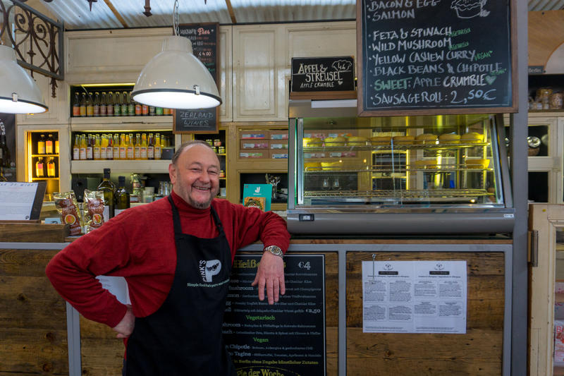 Timothy Pink, a pie purveyor at Markthalle Neun, posing in front of his vendor stand.