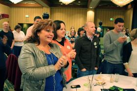 Fourth grade teacher Becky Allen of Boise applauds the first results on election night, indicating Idaho's Props 1, 2 and 3 failed.