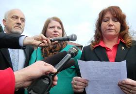Staff Sgt. Robert Bales' wife Karilyn, middle, listens as her sister reads a family statement to reporters at the conclusion of the pretrial hearing.