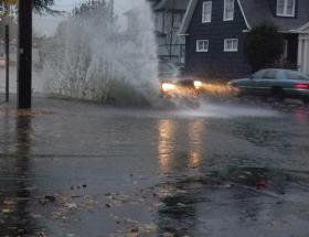 A vehicle speeds through a flooded intersection in Salem.