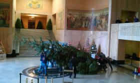 Crews lower the Oregon state capitol Christmas tree to the floor of the rotunda.