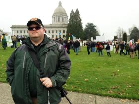 Scott Robertson, carrying an AR-15 style rifle. Robertson says military style rifles and clip capacity are not the problem