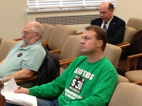 Initiative sponsor Tim Eyman, in a $30 car tabs shirt, listens after testifying in the Washington House Transportation committee against proposed vehicle fee increases.