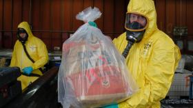A cleanup worker shows off a bag of DDT.