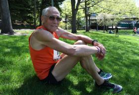Bill Iffrig of Lake Stevens, Wash., rests in the grass after running Bloomsday in Spokane. It was his first race since the Boston Marathon.