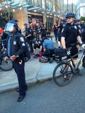 Seattle Police officers face off against protesters downtown. In the background, an unidentified protester is hand-cuffed and placed under arrest.