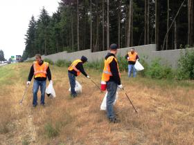 Members of the Street Invasion Ryders motorcycle club pick up trash along I-5 near Olympia. They are members of the state's Adopt-a-Highway volunteer program