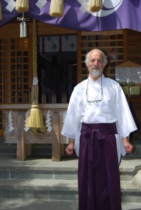 Reverend Koishi Barrish stands in front of the entrance to the Tsubaki Grand Shrine of America. Before the shrine was officially moved here, Rev. Barrish had built his own Shinto shrine in this location.