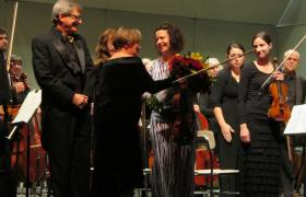 Left to right; Adam Stern, Robin Rilette presents a bouquet to featured soloist, Melia Watras.