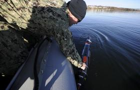 An unmanned underwater sonar vehicle is placed in the water during a Naval exercise.