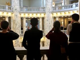 """Add the Words"" protesters encircle the upper level of the rotunda at the Idaho Capitol. They put a hand over their mouth to symbolize how they've been ""silenced"" by lawmakers, who have declined to hold a hearing on an anti-discrimination bill."
