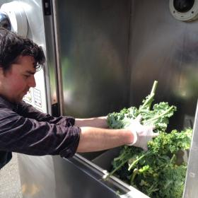 Eric Peterson is a produce clerk at the Redmond, Wash. PCC, he loads some leafy greens into the Harvester.